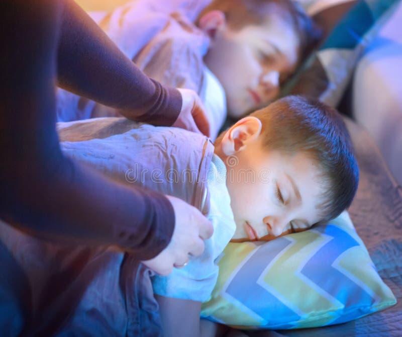 Kinderen die en in een bed slapen dromen stock foto's