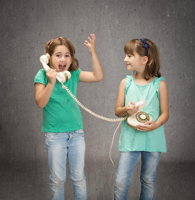 Kinderen die en op telefoon spreken gillen stock foto