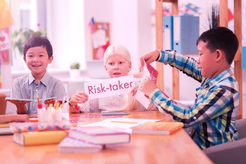 Kinderen die Engelse woorden van bladen van document lezen royalty-vrije stock afbeeldingen