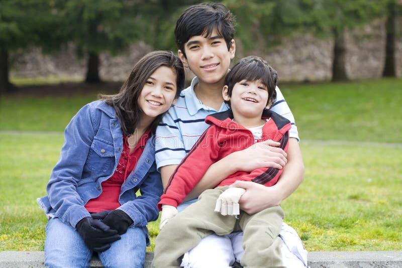 Kinderen die gehandicapte broer behandelen royalty-vrije stock afbeeldingen