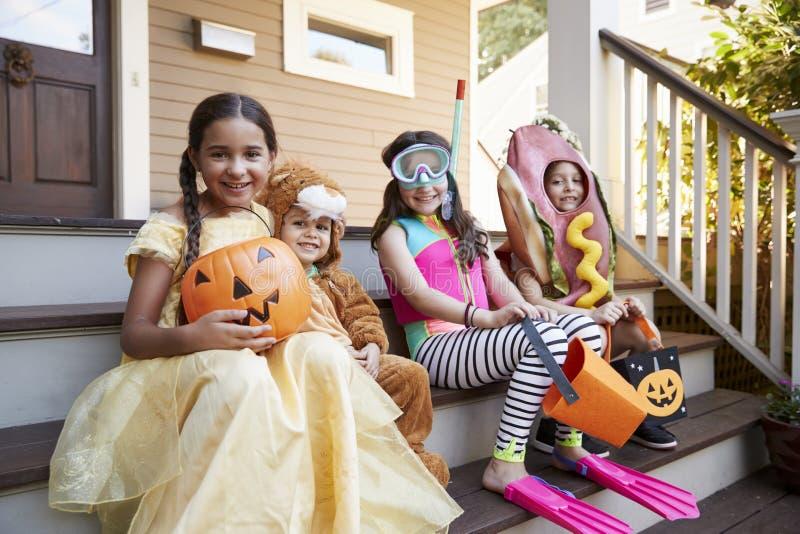 Kinderen die Halloween-Kostuums voor Truc of het Behandelen dragen stock foto