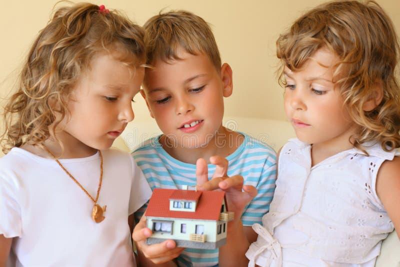Kinderen die in handen model van huis samenblijven stock foto