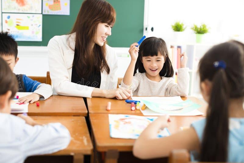 Kinderen die in het klaslokaal en de leraar trekken royalty-vrije stock afbeeldingen