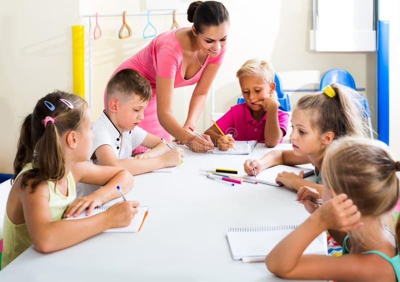Kinderen die het schrijven oefeningen met hulp van leraar in klasse maken stock afbeeldingen