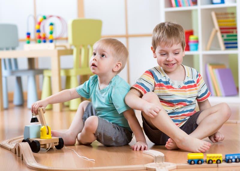 Kinderen die het stuk speelgoed van de spoorweg in speelkamer spelen stock foto's