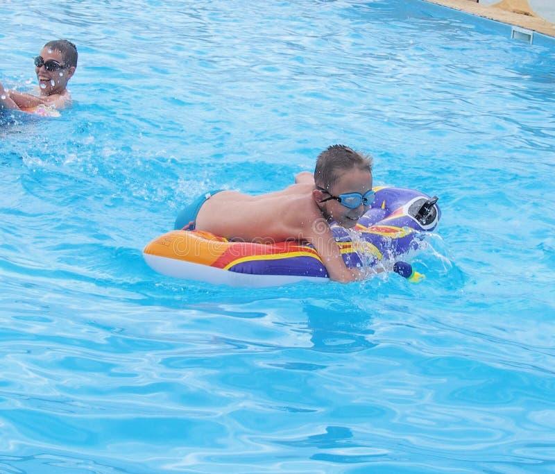 Kinderen die in het zwembad spelen stock fotografie