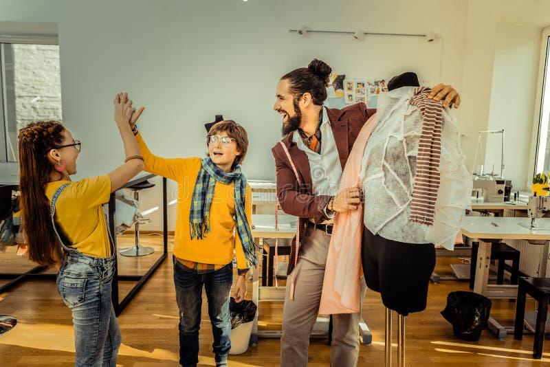 Kinderen die hoogte vijf geven aan elkaar na het succesvolle werk in atelier royalty-vrije stock afbeeldingen