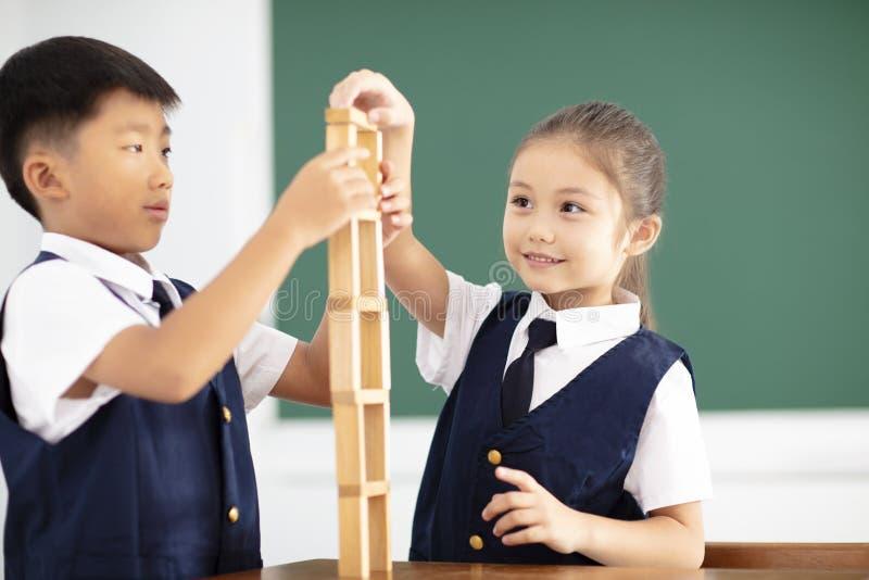 kinderen die houtsneden in klaslokaal spelen stock foto's