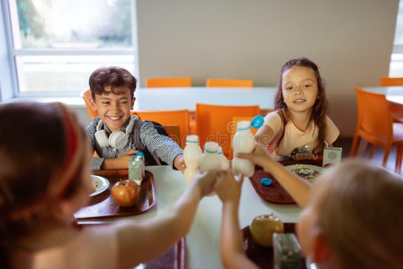 Kinderen die hun flessen sap klinken terwijl het hebben van lunch stock foto