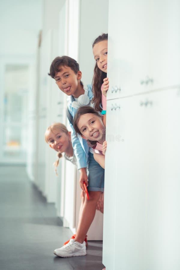 Kinderen die hun tongen tonen terwijl het hebben van pret tijdens onderbreking op school stock afbeelding