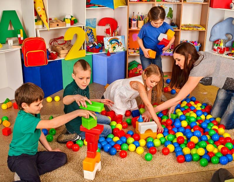 Kinderen die in jonge geitjeskubussen spelen binnen Les in lage school stock afbeeldingen