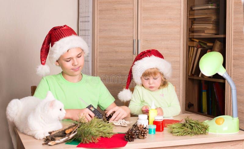 Kinderen die Kerstmisdecoratie met kat op de lijst maken Mak royalty-vrije stock foto's