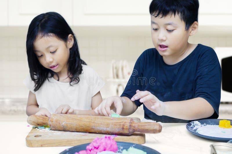 Kinderen die kleurrijk kleistuk speelgoed spelen stock afbeeldingen