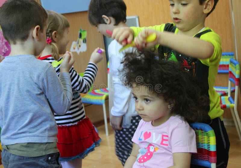 Kinderen die in kleuterschool de kapper spelen royalty-vrije stock afbeelding