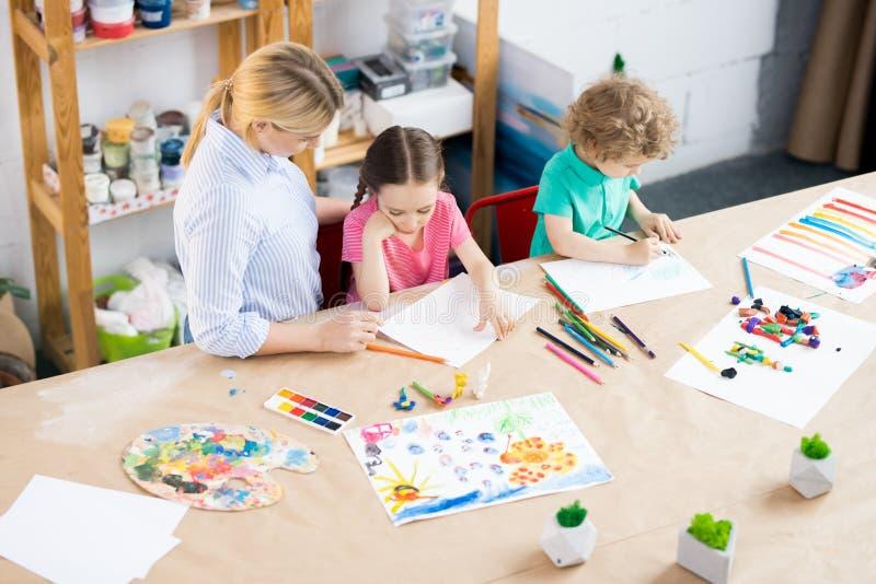 Kinderen die in kunstklasse trekken stock foto's