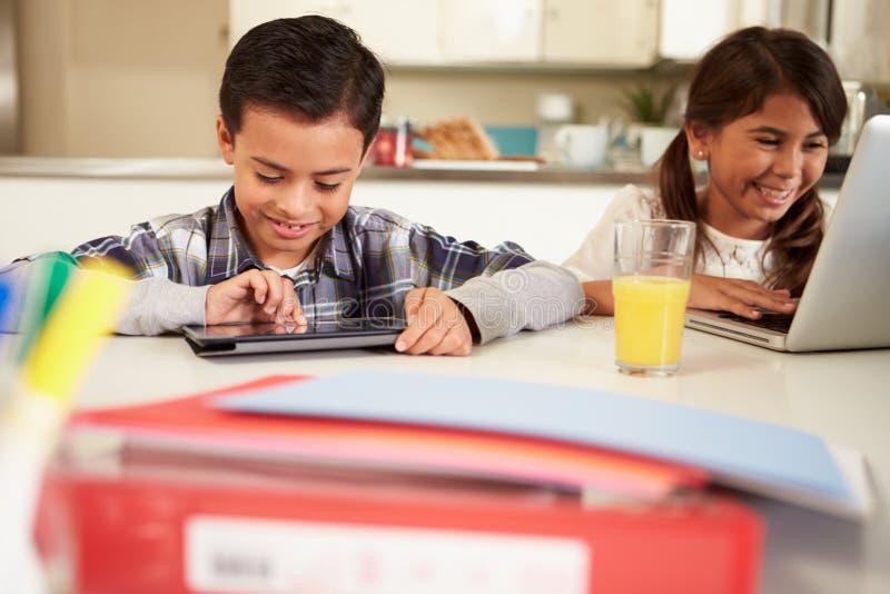 Kinderen die Laptop en Digitale Tablet gebruiken om Thuiswerk te doen stock fotografie