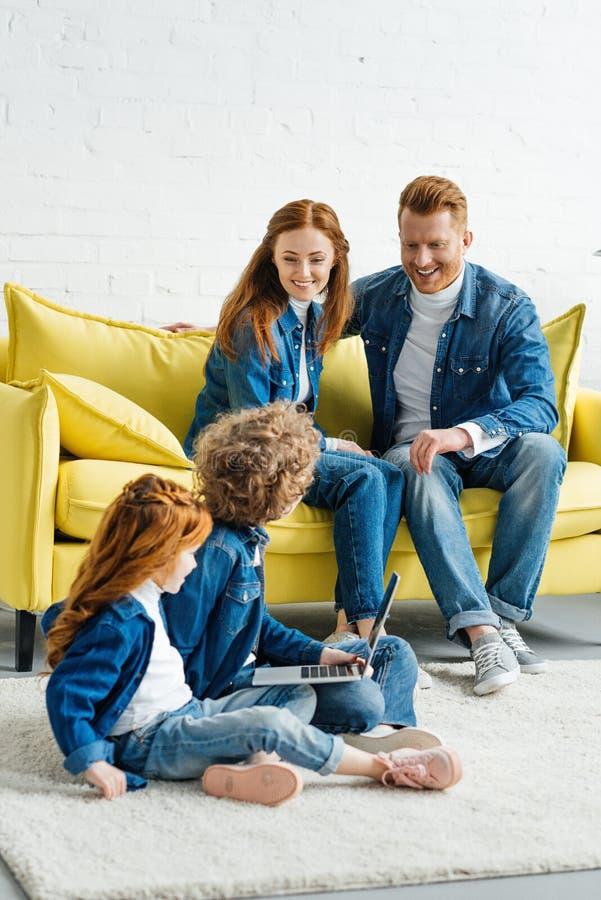 Kinderen die laptop met behulp van terwijl ouders het zitten royalty-vrije stock foto's