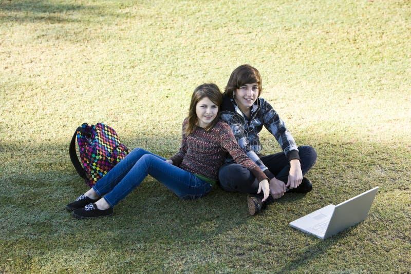 Kinderen die laptop in park met behulp van royalty-vrije stock afbeeldingen