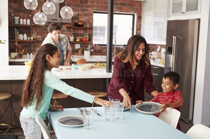 Kinderen die Lijst helpen te leggen Klaar voor Familiemaaltijd royalty-vrije stock afbeeldingen