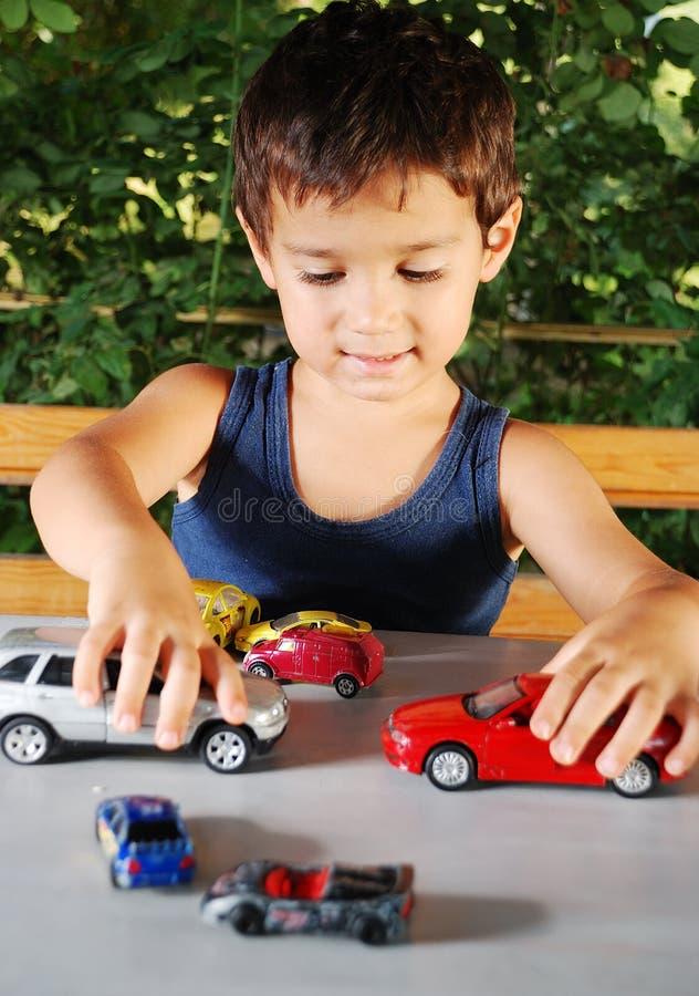Kinderen die met auto'sspeelgoed openlucht spelen in de zomer stock afbeelding