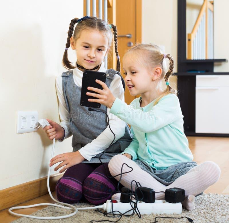 Kinderen die met contactdozen en elektriciteit binnen spelen stock afbeeldingen