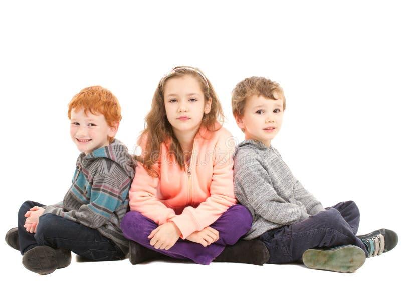 Kinderen die met de benen over elkaar op vloer zitten royalty-vrije stock afbeelding