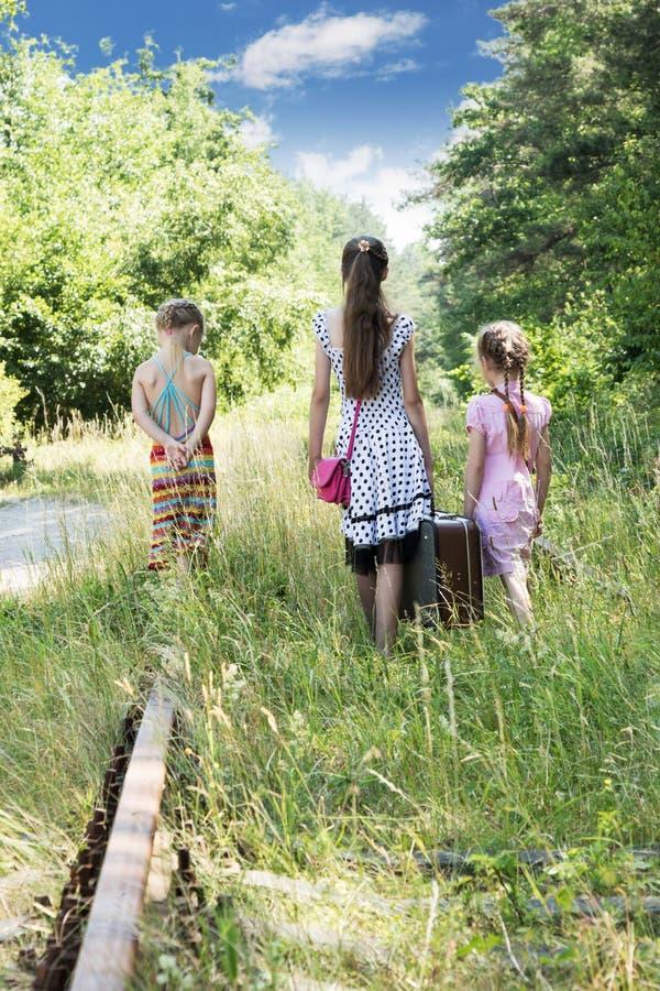 Kinderen die met een koffer bij de spoorweg lopen stock afbeeldingen