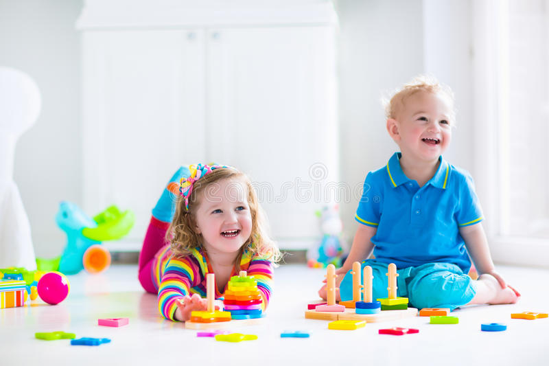 Kinderen die met houten speelgoed spelen royalty-vrije stock afbeeldingen
