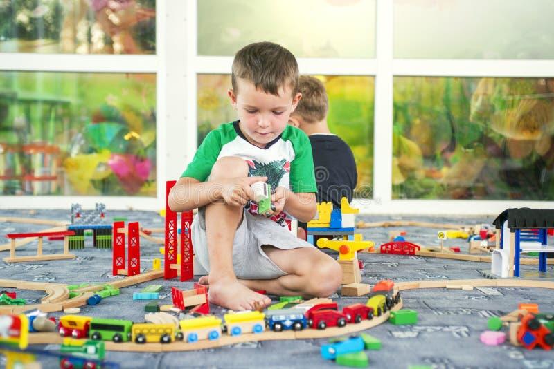 Kinderen die met houten trein spelen Het spel van de peuterjongen met trein en auto's Onderwijsspeelgoed voor kleuterschool en kl royalty-vrije stock fotografie