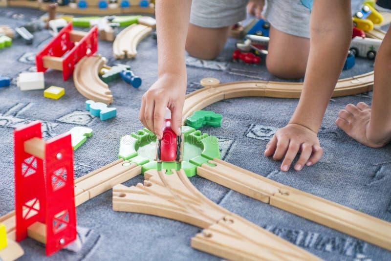 Kinderen die met houten trein spelen Het spel van de peuterjongen met trein en auto's Onderwijsspeelgoed voor kleuterschool en kl stock foto