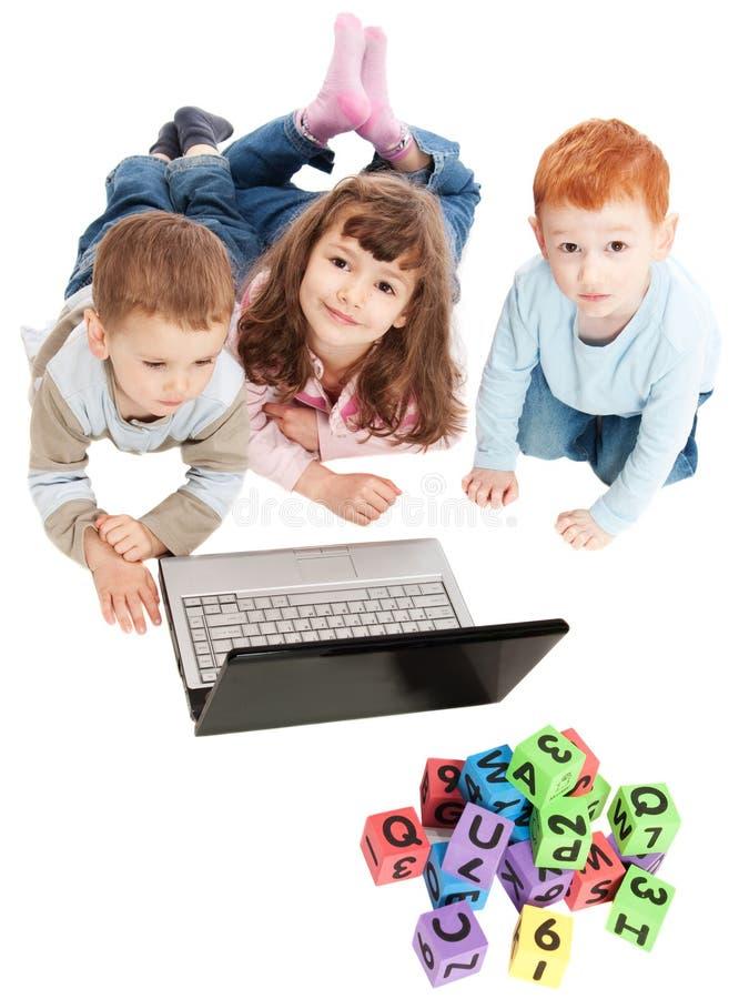 Kinderen die met jonge geitjesblokken en computer leren stock afbeeldingen