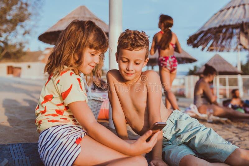 Kinderen die met mobiele telefoon op zandig strand spelen stock foto