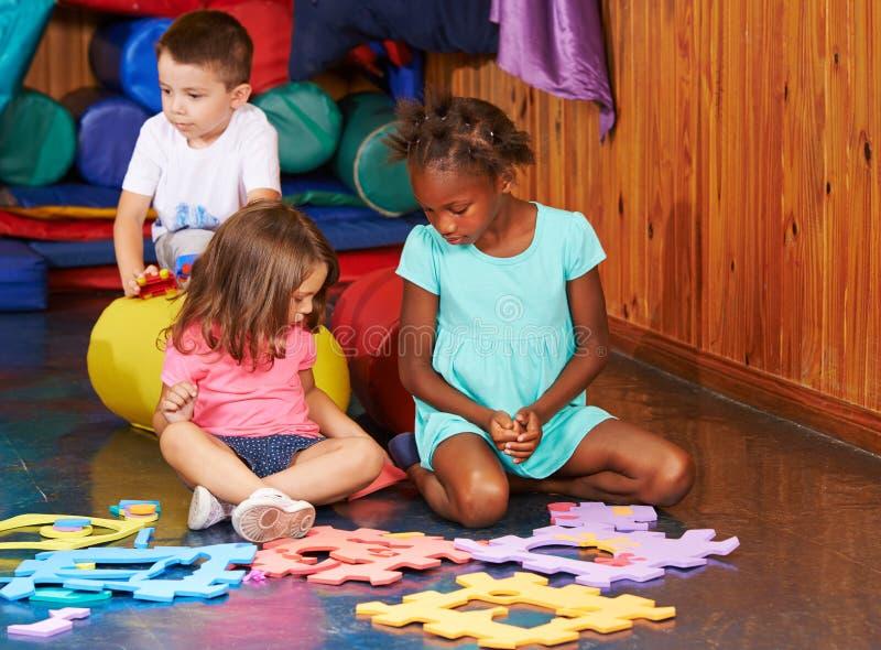 Kinderen die met puzzel in kleuterschool spelen royalty-vrije stock fotografie