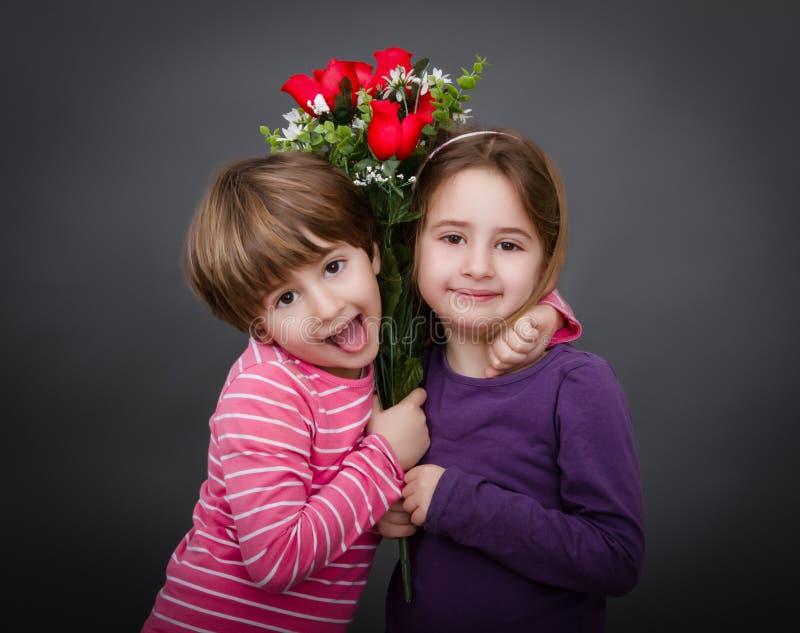 Kinderen die met rode rozen omhelzen stock foto's