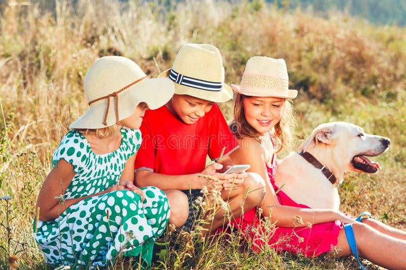 Kinderen die met slimme telefoon spelen stock afbeeldingen