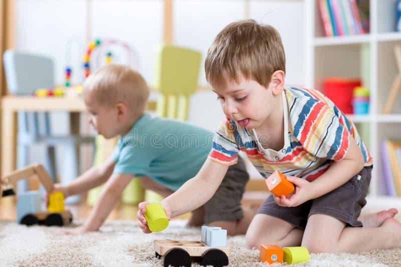 Kinderen die met speelgoed in kleuterschool of opvang of huis spelen stock afbeeldingen