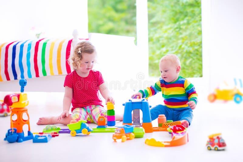 Kinderen die met stuk speelgoed auto's spelen stock foto