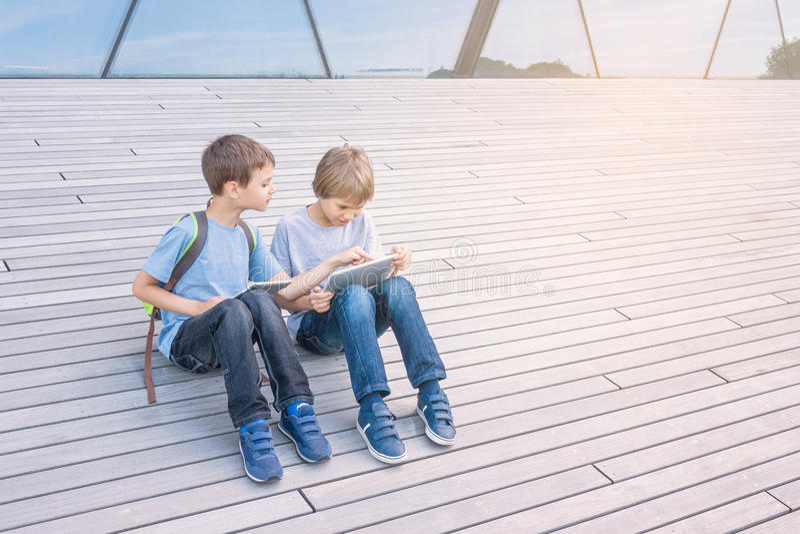 Kinderen die met tabletcomputer spelen openlucht Mensenonderwijs het leren het concept van de technologievrije tijd royalty-vrije stock foto