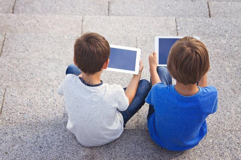 Kinderen die met tablettencomputers zitten Achter mening Onderwijs, het leren, technologie, vrienden, schoolconcept royalty-vrije stock fotografie