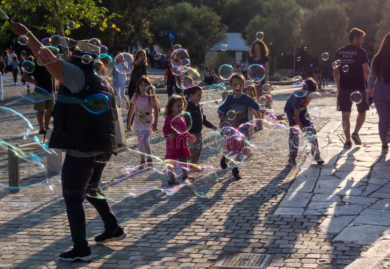 Kinderen die met zeep bubles in het licht van zonsondergang spelen royalty-vrije stock afbeelding