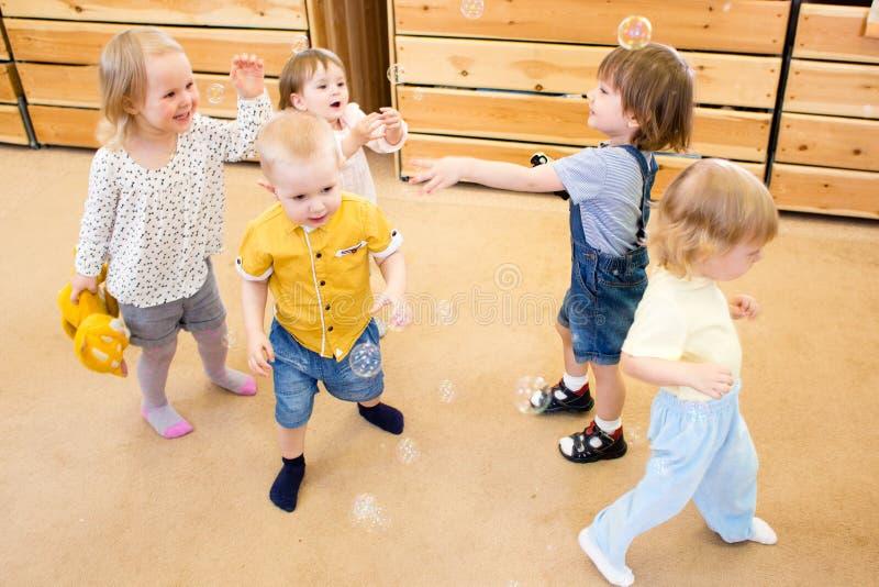 Kinderen die met zeepbels in kleuterschool spelen royalty-vrije stock afbeelding