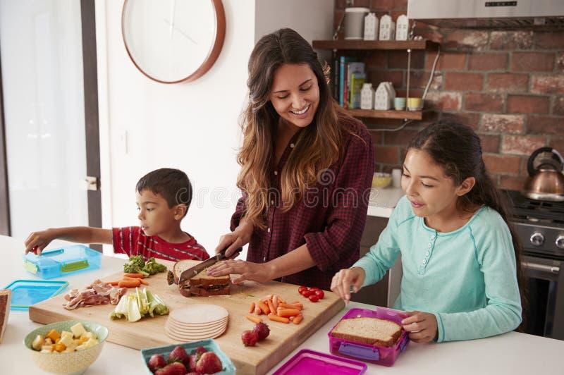 Kinderen die Moeder helpen om Schoolmaaltijden in Keuken thuis te maken royalty-vrije stock afbeeldingen