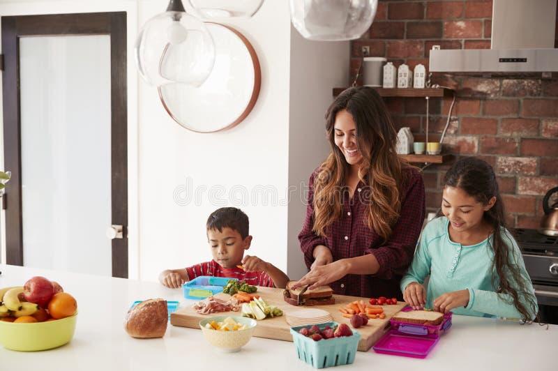 Kinderen die Moeder helpen om Schoolmaaltijden in Keuken thuis te maken royalty-vrije stock foto's