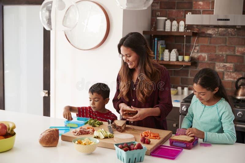 Kinderen die Moeder helpen om Schoolmaaltijden in Keuken thuis te maken stock foto's