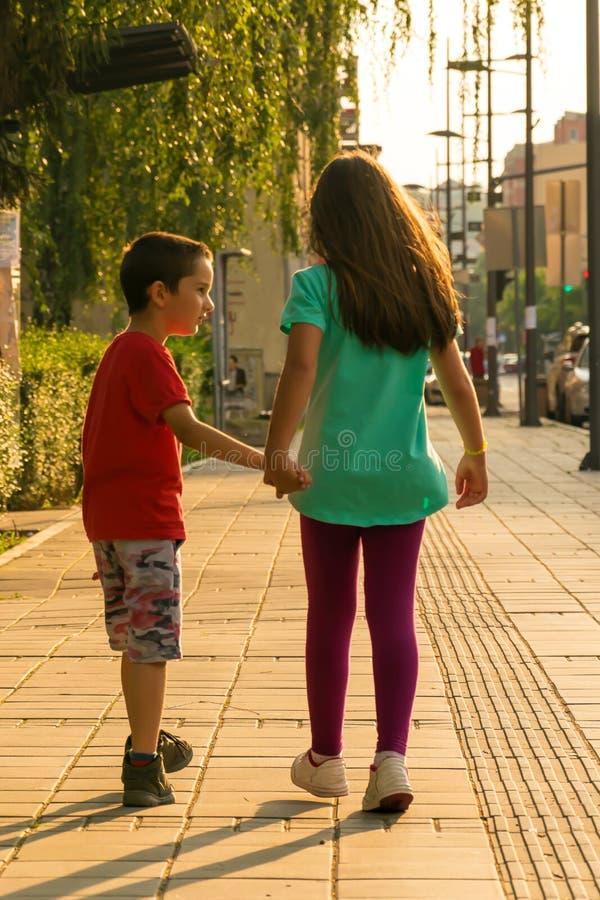 Kinderen die onderaan de handen van de straatholding lopen stock foto's