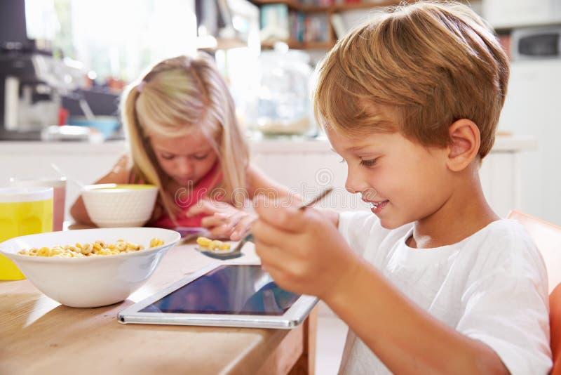 Kinderen die Ontbijt eten terwijl het Gebruiken van Digitale Tablet stock foto