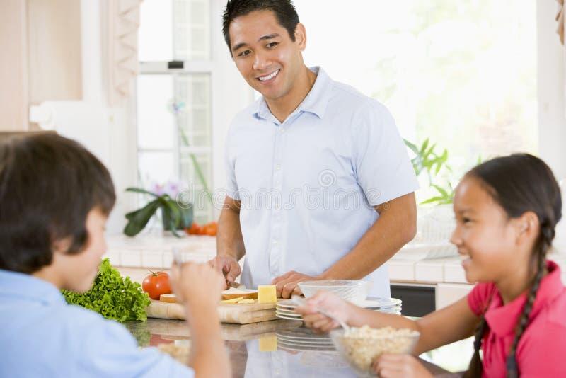 Kinderen die Ontbijt hebben terwijl de Papa Voedsel voorbereidt royalty-vrije stock afbeelding