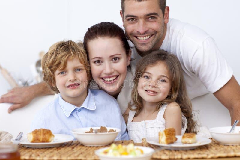 Kinderen die ontbijt met hun ouders hebben stock afbeeldingen