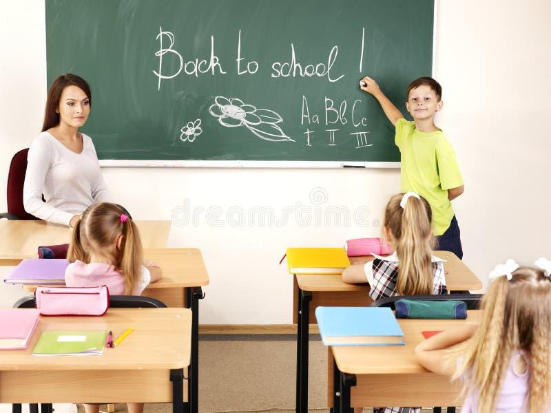 Kinderen die op bord schrijven. stock afbeeldingen