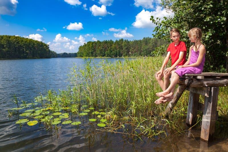 Kinderen die op een pijler door een de zomermeer zitten royalty-vrije stock foto